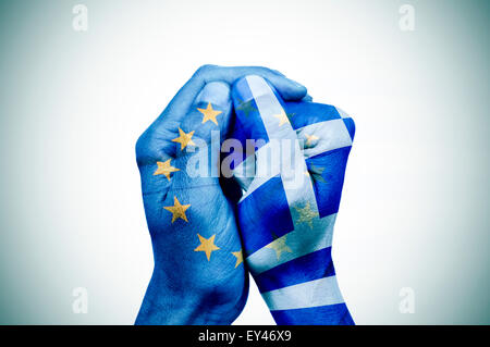 hand patterned with the flag of the European Community envelops another hand patterned with the flag of Greece - Stock Photo