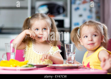 Children drinking and eating at daycare - Stock Photo