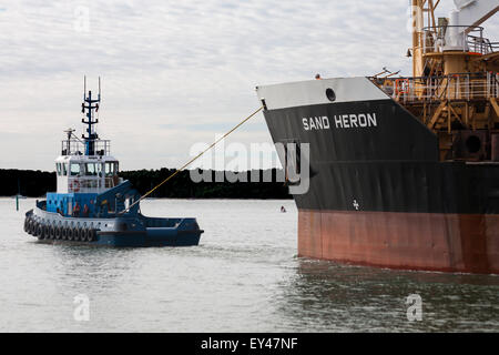 Tug pulling Sand Heron vessel out of Poole Harbour in July - Stock Photo
