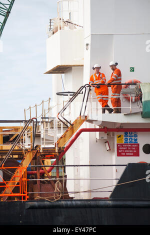 Workers in high visibility clothing on Sand Heron vessel at Poole Harbour in July - Stock Photo