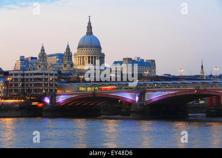 Blackfriars Railway Bridge, in front of St Paul's Cathedral, across the River Thames, at dusk, in London, UK - Stock Photo