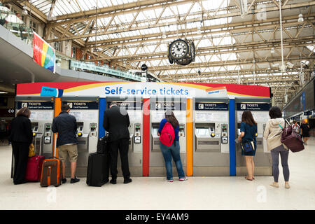 People buying rail tickets from a self service ticket booth, Waterloo railway station London UK - Stock Photo