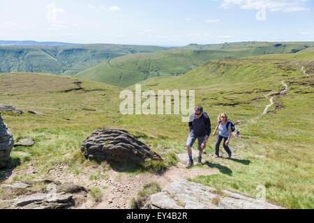 Walkers walking up Grindslow Knoll, on Kinder Scout, Derbyshire, Peak District, England, UK - Stock Photo