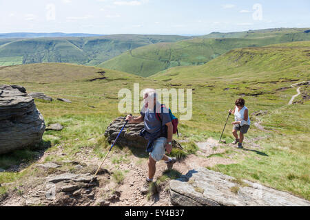 Hill walkers in the English countryside during Summer walking up Grindslow Knoll on Kinder Scout, Derbyshire, Peak - Stock Photo