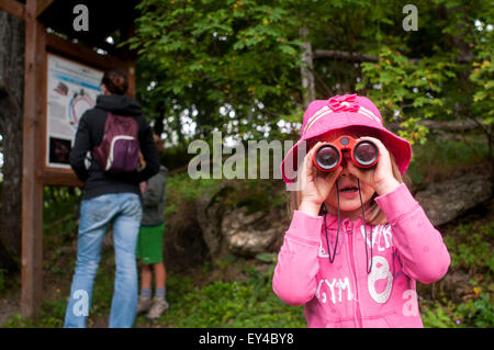 Young Girl Looking Through Binoculars While Woman and Young Boy Look at Hiking Map - Stock Photo