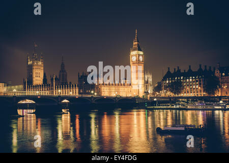 View of Big Ben and Westminster across Thames River at night.  This image has a retro filter effect - Stock Photo
