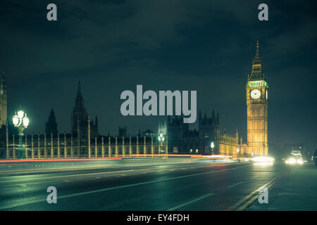 View of Big Ben in London across Westminster Bridge on a damp night - Stock Photo
