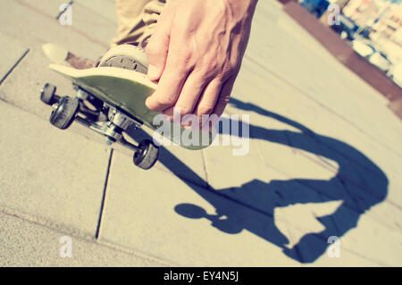 closeup of a young man performing a trick with his skateboard, with a filter effect - Stock Photo