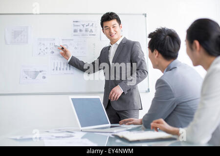 Young business person talking in meeting - Stock Photo