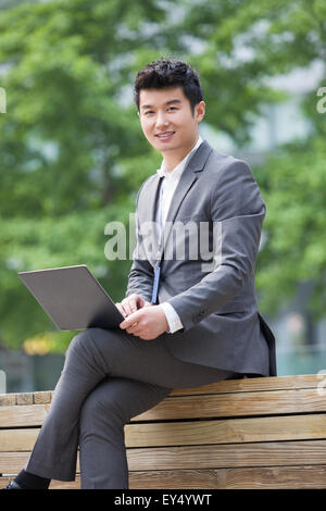 Young businessman working with laptop outdoors - Stock Photo