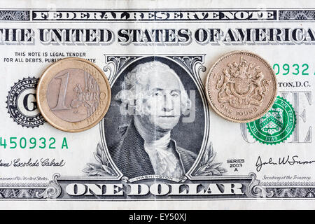 One British Pound sterling coin and one Euro coin on a US American dollar bill used as background. Exchange rates. - Stock Photo
