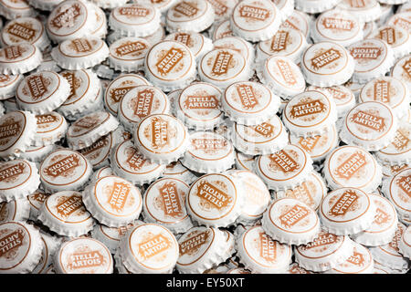 Pile of Stella Artois disregarded bottle tops, Stella Artois logo in gold on each top - Stock Photo