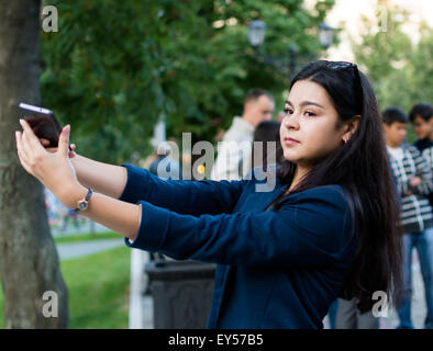 Young woman with dark hair prepares to take a selfie with her smartphone at a public fountain display in Ufa Russia - Stock Photo