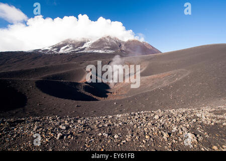 Volcano smoking crater on side of Mount Etna Sicily Italy in black lava field. - Stock Photo