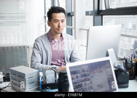 Male photographer working in office with computer - Stock Photo