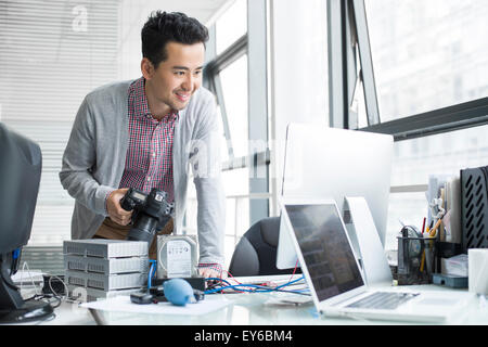 Male photographer working in office - Stock Photo