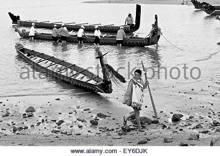 Members of a waka (traditional Maori canoe) crew bring their boat back to shore after attending Waitangi Day annual - Stock Photo