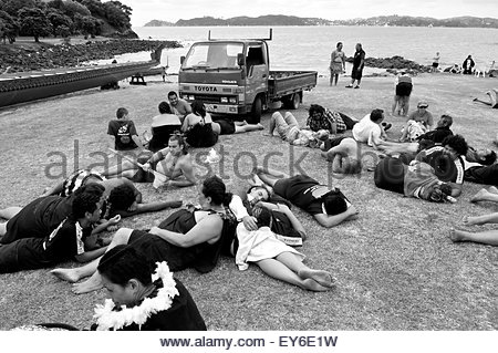 Members of a waka (traditional Maori canoe) crew rest after participating in  Waitangi Day annual commemorations - Stock Photo