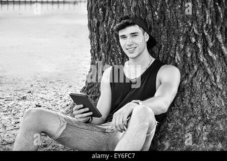 Smiling Young Handsome Man, Reading on Ebook Reader or Holding a Tablet Computer, Relaxing on Grassy Ground at Park, - Stock Photo
