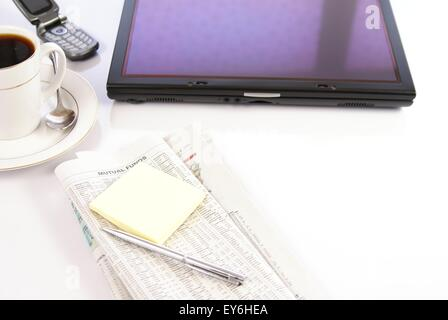 Office desk with older convertible tablet PC computer, newspapers, coffee and phone - Stock Photo