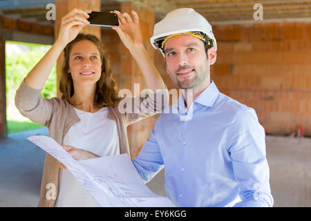 View of a Young woman and architect on construction site - Stock Photo