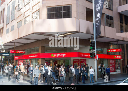 pedestrians waiting to cross the road in Pitt street outside branch of St george bank,Sydney,Australia - Stock Photo