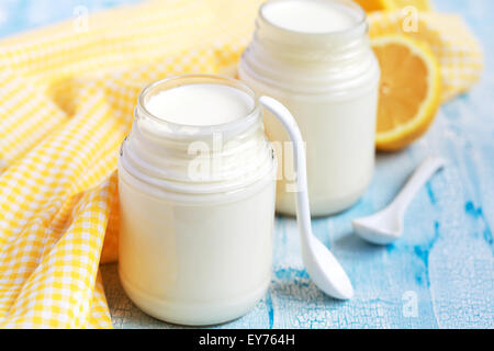 Homemade yogurt in two small glass jars on a blue table, selective focus - Stock Photo