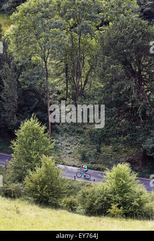 Cyclist rides along a country road shot from above - Stock Photo