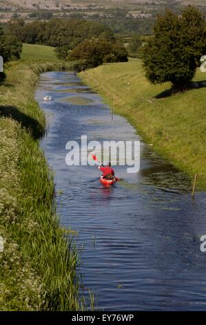 Kayaking on the northern reaches of the Lancaster Canal, not navigable by narrowboats. Cumbria, England. - Stock Photo