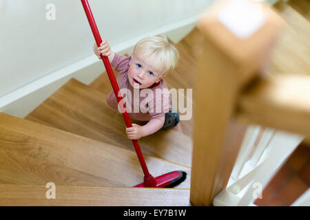 Young boy, 2 years, sweeping a staircase with a broom. - Stock Photo