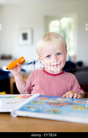 Young boy reading a childrens book with an electronic tiptoi pen, which explains the content of the book to the - Stock Photo