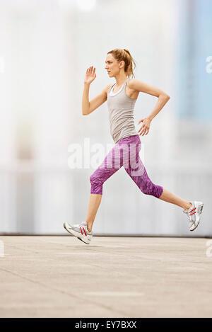 Mid adult woman running - Stock Photo