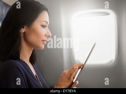 Young woman using tablet on plane - Stock Photo