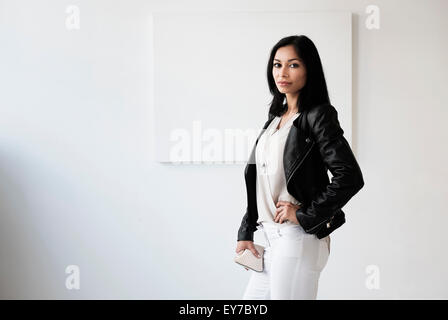 Portrait of young woman in studio - Stock Photo