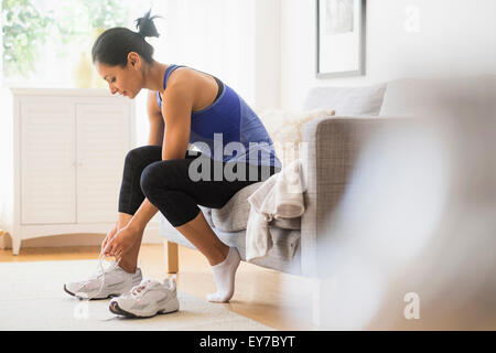 Young woman putting on shoes - Stock Photo
