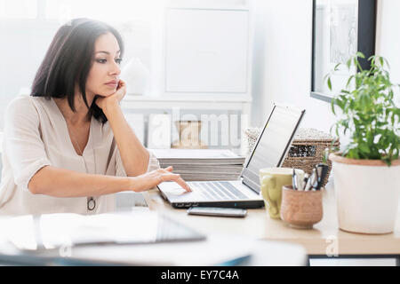 Woman sitting at desk with laptop - Stock Photo