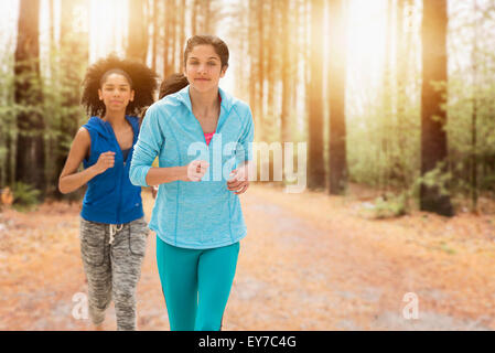 Portrait of teenage girls (14-15, 16-17) running - Stock Photo