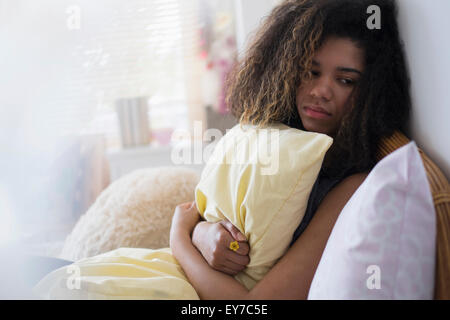 Teenage girl (14-15) sitting on bed, embracing pillow - Stock Photo