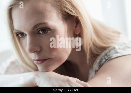 Pensive mid-adult woman lying on bed - Stock Photo