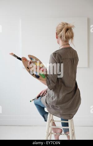 Female artist painting in studio - Stock Photo