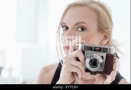 Woman holding digital camera - Stock Photo