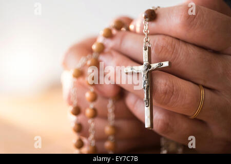 Woman praying with rosary beads in hands - Stock Photo