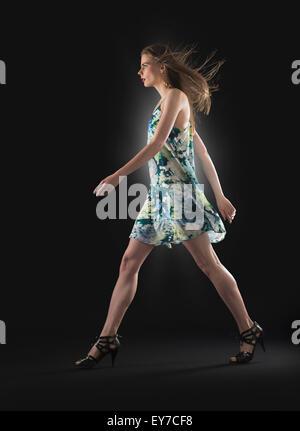 Studio shot of young woman walking - Stock Photo