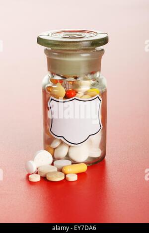 Pills in front of glass chemical bottle with blank label, filled with colorful pills - Stock Photo