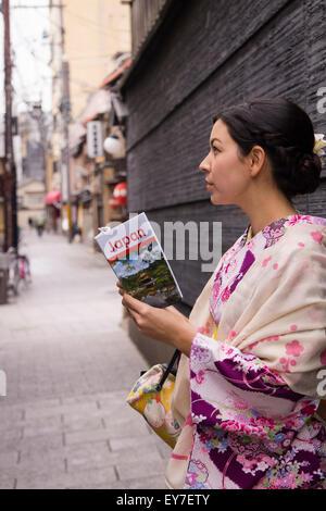 A young lady renting a kimono, enjoying walking around Gion, Kyoto. - Stock Photo