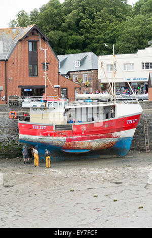 A fishing trawler in dry dock in Padstow harbour Cornwall UK being cleaned and maintained - Stock Photo