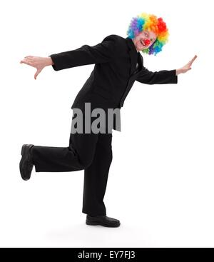 Happy business man wearing colorful clown hair and standing in a funny posture - Stock Photo