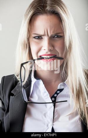 Portrait of businesswoman biting eyeglasses - Stock Photo
