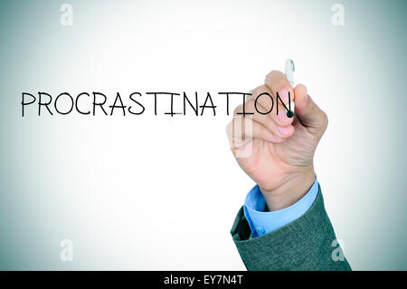 closeup of the hand of a man writing the word procrastination in the foreground - Stock Photo