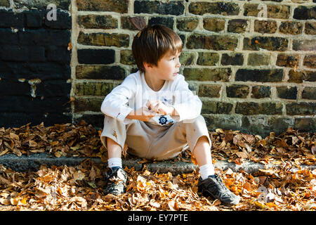 4 to 6 year old Caucasian boy, outdoors. Sitting in street on piles of autumn leaves, looking to the side - Stock Photo